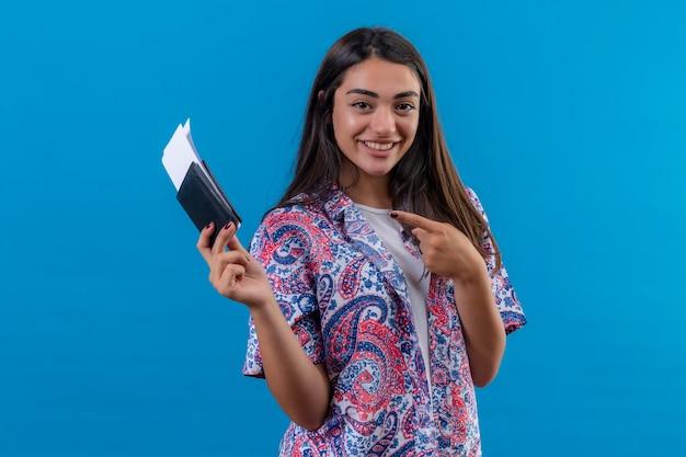 Młoda piękna kobieta turysta trzyma paszport z biletów patrząc na kamery, wskazując palcem wskazującym do nich uśmiechnięty wesoło stojąc na na białym tle niebieskim tle