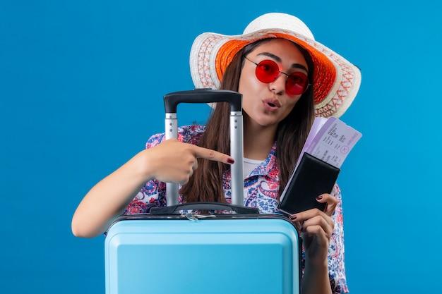 Młoda piękna kobieta turysta w letnim kapeluszu i czerwonych okularach przeciwsłonecznych, trzymając walizkę podróżną i bilety z paszportem, wskazując palcem na wyglądającego pozytywnie i szczęśliwie na niebieskim b