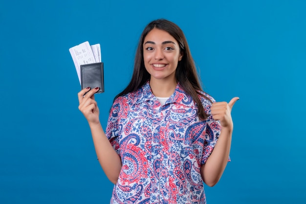 Młoda piękna kobieta turystka posiadająca paszport z biletami patrząc na kamery, uśmiechnięta wesoło, pokazująca kciuki do góry gotowa na wakacje stojąca na odosobnionym niebieskim tle