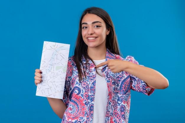Młoda piękna kobieta turystka trzymająca mapę patrząc na kamerę z radosną twarzą, wskazującą na nią palcem wskazującym, uśmiechnięta wesoło stojąc na odizolowanym niebieskim tle