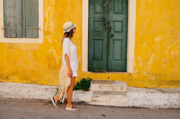 Młoda piękna kobieta turystyczna idzie wzdłuż ulicy w starym greckim mieście. grecja. zwiedzanie kefalonii. koncepcja podróży i wakacji.