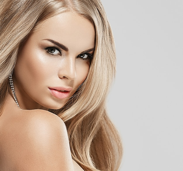 Młoda piękna kobieta twarz portret ze zdrową skórą długie kręcone blond włosy