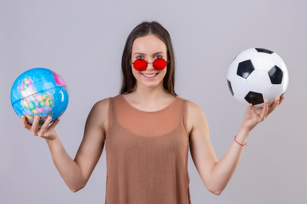 Młoda piękna kobieta ubrana w czerwone okulary przeciwsłoneczne, trzymając piłkę nożną i kula ziemska, patrząc na kamery z szczęśliwą twarzą uśmiechniętą stojącą na białym tle