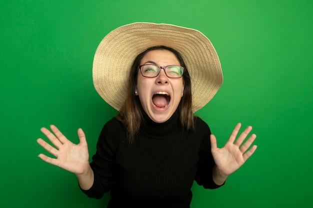 Młoda piękna kobieta ubrana w letni kapelusz w czarnym golfie i okularach krzycząc z podniesionymi rękami stojąc na zielonej ścianie