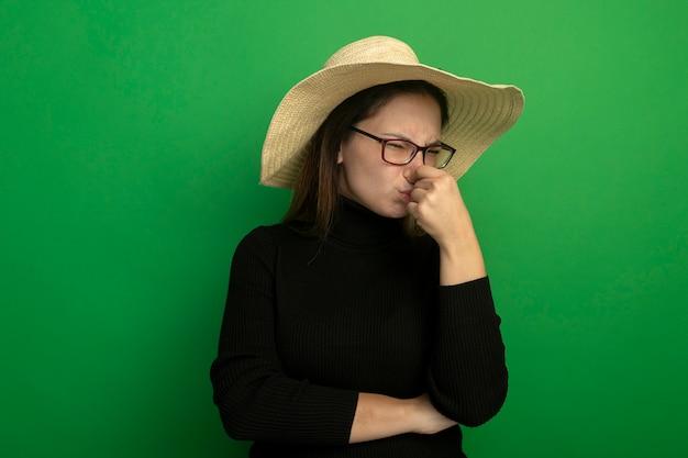 Młoda piękna kobieta ubrana w letni kapelusz w czarnym golfie i okularach zamykających nos z zirytowanym wyrazem twarzy na zielonej ścianie