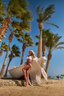 Młoda piękna kobieta ubrana w pareo i strój kąpielowy stojąc na plaży w pobliżu białej łodzi