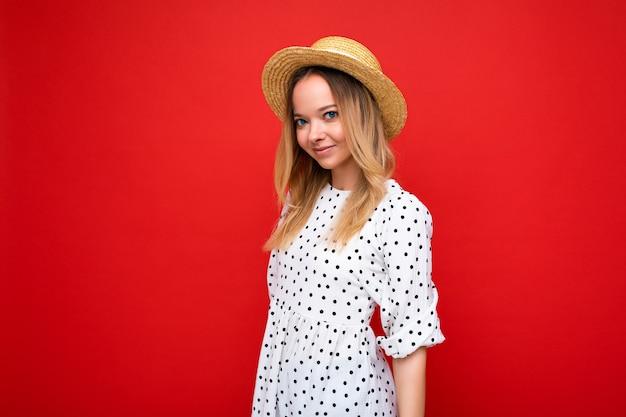 Młoda piękna kobieta ubrana w sukienkę i słomkowy kapelusz