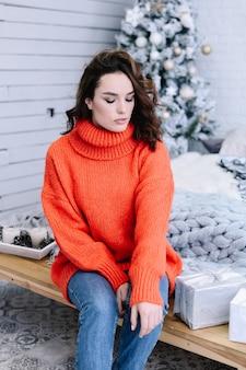 Młoda piękna kobieta ubrana zimowy sweter w domu