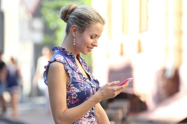 Młoda piękna kobieta uśmiecha się patrząc na telefon komórkowy