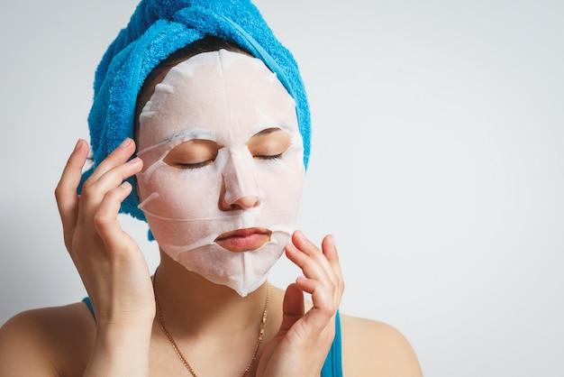 Młoda piękna kobieta używa nawilżającej maseczki kosmetycznej z ręcznikiem owiniętym wokół głowy. na białej ścianie.