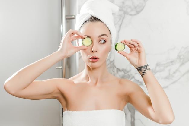Młoda piękna kobieta używa plasterka ogórka na oczy owinięte w ręczniki w łazience