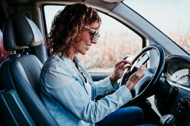 Młoda piękna kobieta używa telefon komórkowego w samochodzie. koncepcja podróży