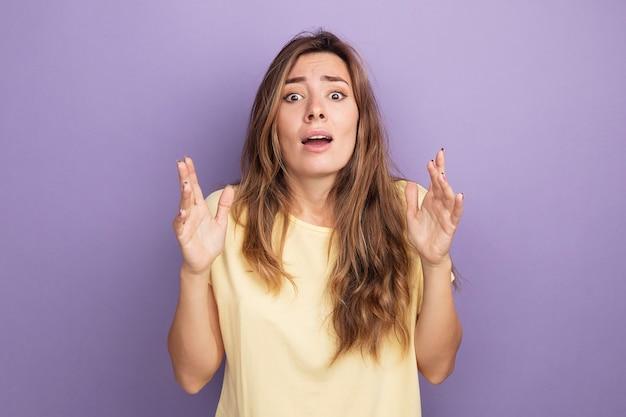 Młoda piękna kobieta w beżowej koszulce, patrząc na kamerę, zmartwiona i przerażona, podnosząca ręce