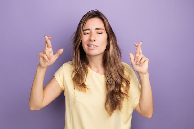 Młoda piękna kobieta w beżowej koszulce spełniającej pożądane życzenie z zamkniętymi oczami krzyżującymi palce stojące nad fioletem