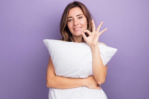 Młoda piękna kobieta w beżowej koszulce trzymająca białą poduszkę patrząca na kamerę z uśmiechem na twarzy robi ok znak