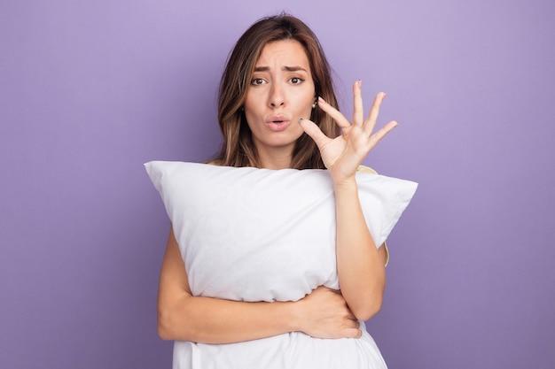Młoda piękna kobieta w beżowym t-shirt trzymając białą poduszkę patrząc na kamery zdezorientowany i zmartwiony, pokazując mały rozmiar gest palcami, koncepcja środka symbolu