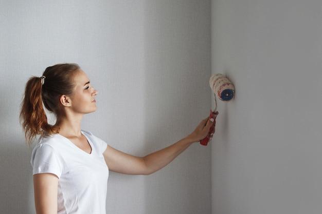 Młoda piękna kobieta w białej koszulce maluje wałkiem ścianę w nowym mieszkaniu podczas remontu