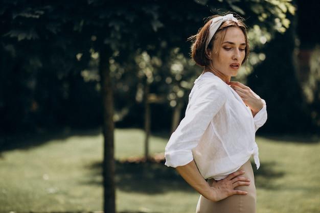 Młoda piękna kobieta w białej koszuli na podwórku