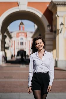 Młoda piękna kobieta w białej spódnicy i czarnej koszuli w mieście.