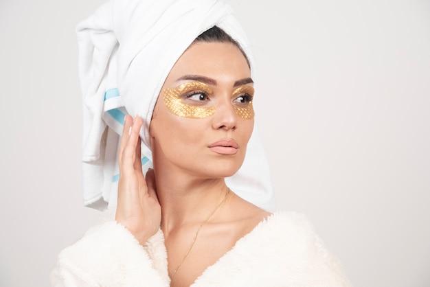 Młoda piękna kobieta w biały ręcznik i szlafrok z przepaską na oku.
