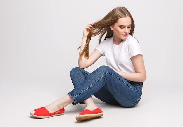 Młoda piękna kobieta w biały t-shirt i dżinsy na białym tle. młoda kobieta siedzi na białym tle. koncepcja fotografii reklam odzieży i butów.