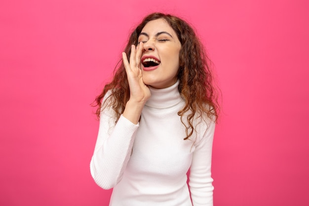 Młoda piękna kobieta w białym golfie krzyczy lub dzwoni trzymając rękę nad ustami stojąc nad różową ścianą