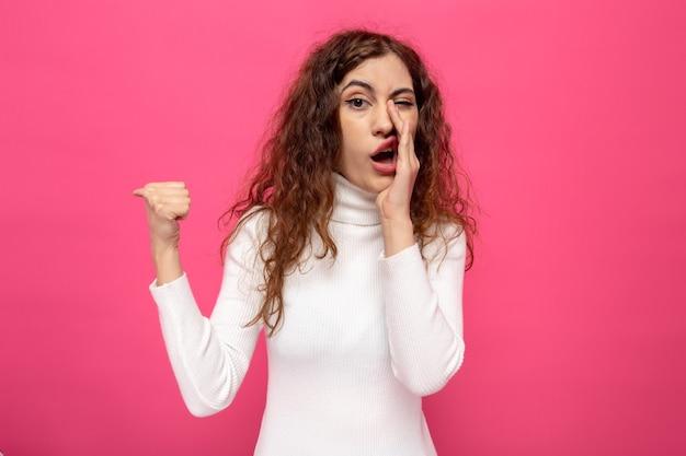 Młoda piękna kobieta w białym golfie opowiadająca sekretnie trzymająca dłoń na ustach wskazująca kciukiem w bok, stojąca na różu
