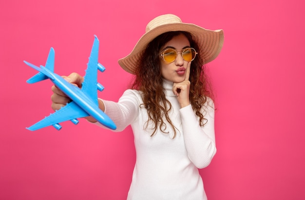 Młoda piękna kobieta w białym golfie w żółtych okularach i letnim kapeluszu trzymająca samolocik, patrząc na bok z zamyślonym wyrazem myślenia stojącego na różowo