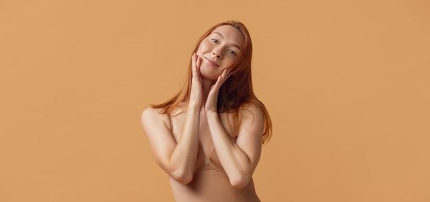 Młoda piękna kobieta w bieliźnie pozowanie na białym tle na ścianie pastelowych studio. naturalne piękno