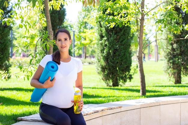 Młoda piękna kobieta w ciąży jest zaangażowana w fitness w parku.