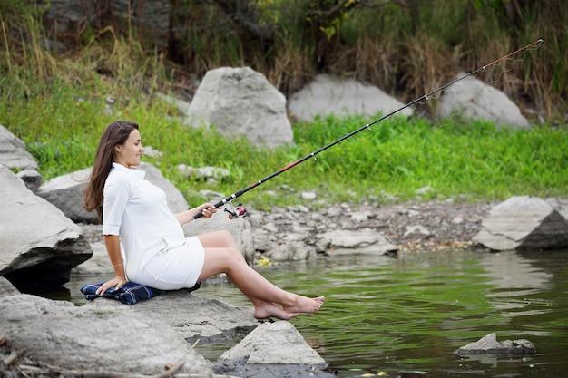 Młoda piękna kobieta w ciąży łowi ryby na brzegu rzeki