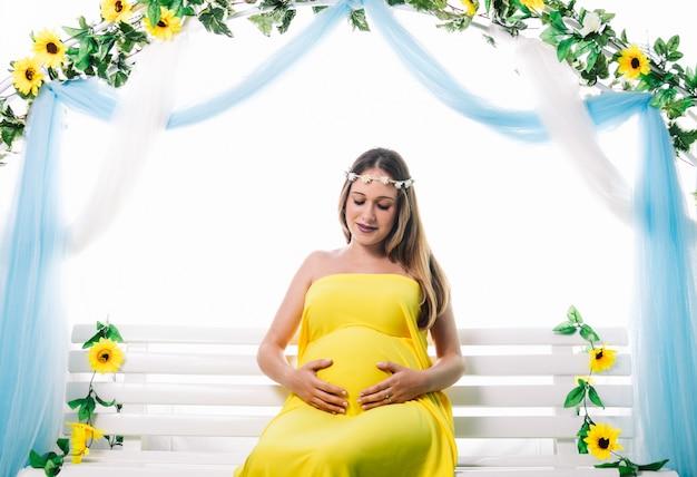 Młoda piękna kobieta w ciąży pozuje. patrząc na jej brzuch