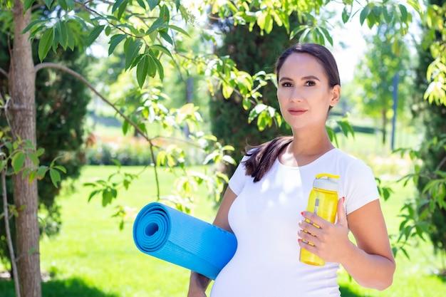 Młoda piękna kobieta w ciąży w białej koszulce jest zaangażowana w fitness w parku. trzyma matę do jogi i sportu oraz butelkę czystej wody