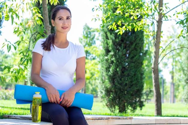 Młoda piękna kobieta w ciąży w białej koszulce jest zaangażowana w fitness w parku. trzymając matę do jogi i sportu oraz butelkę czystej wody
