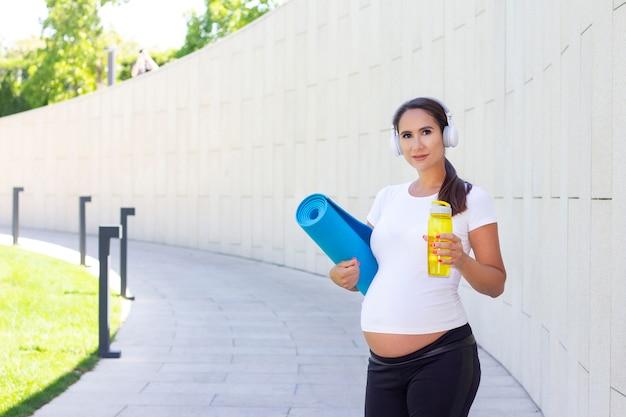 Młoda piękna kobieta w ciąży w białej koszulce jest zaangażowana w fitness