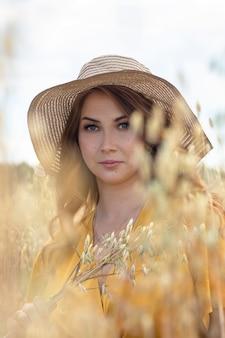 Młoda piękna kobieta w ciąży w żółtej sukience i kapeluszu idzie przez pole pszenicy pomarańczy w słoneczny letni dzień