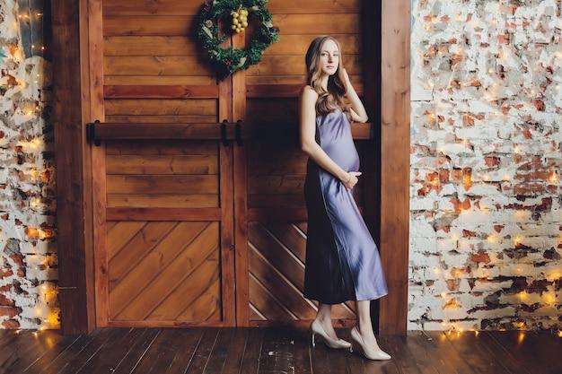 Młoda piękna kobieta w ciąży z blond włosami i delikatnym makijażem w modnej czerwonej sukience pozowanie w pobliżu studia