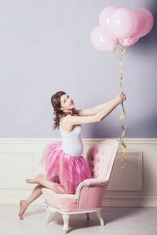 Młoda piękna kobieta w ciąży z różowymi balonami i różową spódnicą baletową na tle retro
