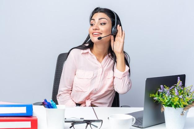 Młoda piękna kobieta w codziennych ubraniach ze słuchawkami i mikrofonem siedzi przy stole z laptopem trzymając rękę nad uchem uśmiechając się nad białą ścianą pracując w biurze