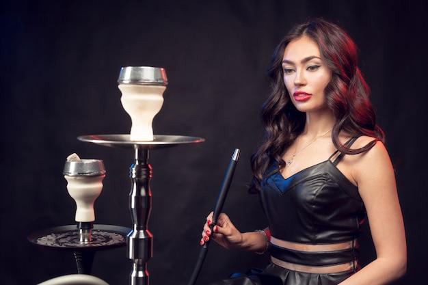 Młoda piękna kobieta w czarnej sukni palenia i wydech fajki