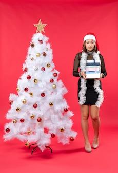 Młoda piękna kobieta w czarnej sukni z czapką świętego mikołaja i ozdobioną choinką, trzymając prezenty