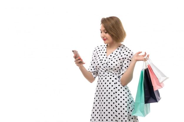 Młoda piękna kobieta w czarno-białej groszki z widokiem z przodu trzyma paczki z zakupami za pomocą telefonu