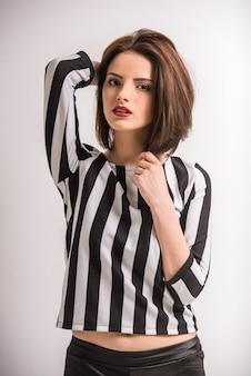Młoda piękna kobieta w czarno-białej koszuli patrząc