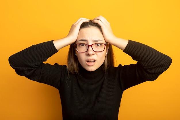 Młoda piękna kobieta w czarnym golfie patrząc na przód mylić z rękami na głowie za błąd stojąc na pomarańczowej ścianie