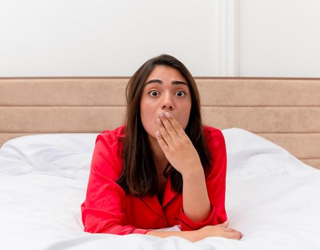 Młoda piękna kobieta w czerwonej piżamie r. na łóżku patrząc na kamery jest w szoku obejmując usta ręką we wnętrzu domu na jasnym tle