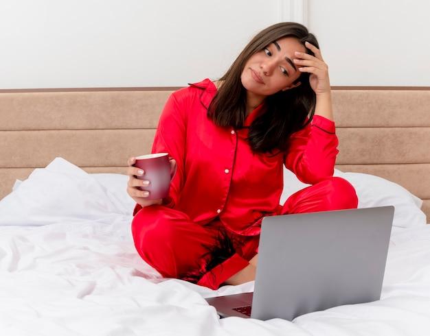 Młoda piękna kobieta w czerwonej piżamie siedzi na łóżku z laptopem i filiżanką kawy, wyglądająca na zdezorientowaną i niezadowoloną we wnętrzu sypialni na jasnym tle