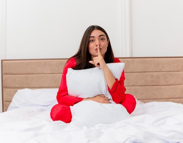 Młoda piękna kobieta w czerwonej piżamie siedzi na łóżku z poduszką, robiąc gest ciszy palcem na ustach we wnętrzu sypialni