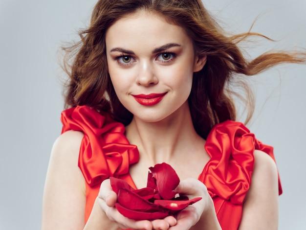 Młoda piękna kobieta w czerwonej sukience z dużym kwiatem róży