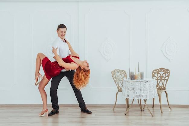 Młoda piękna kobieta w czerwonej sukni i mężczyzna tanu odizolowywającym na białym tle.