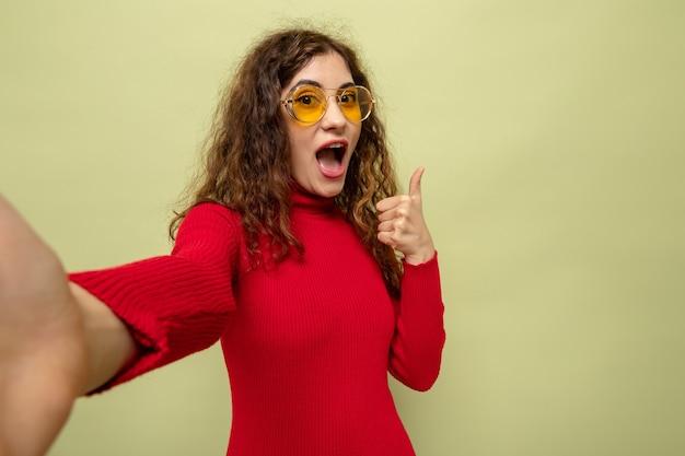 Młoda piękna kobieta w czerwonym golfie w żółtych okularach patrząca z przodu szczęśliwa i zdziwiona pokazując kciuk do góry stojący nad zieloną ścianą